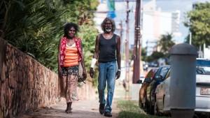 """Banned"" woman, Faith (Jennifer Budukpuduk Gaykamangu) and Charlie (David Gulpilil) walk around the city (Darwin) in Charlie's Country, courtesy of Monument Releasing"