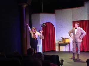 Rosemary Fenton pretend to be a tree, to avoid the attention of a deadly poisonous spider, as Bullshot Crummond (Tyler Ward) watches in Randall Theater's Bullshot Crummond.