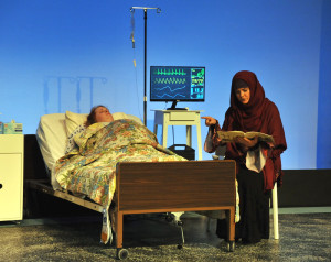 Adoptive-mother-to-be Sahrrah Shouman (Stephanie Jones) reads children's story to unborn child of pregnant, brain dead, on life support Claire Green (Elizabeth Marie) in Camelot Theatre's production of Solomon's Blade