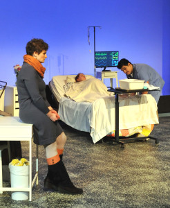 Sister-in-law Tamara Greenwood (Rose Passione), conversing with nurse Steve Borrego (Rigo Jimenez) attending to pregnant, brain dead, on life support Claire Green (Elizabeth Marie) in Camelot Theatre's production of Solomon's Blade