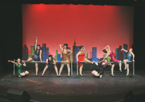 """Women's ensemble (led by Haley Forysth in gold sequin dress, Rebecca Campbell in red sequined dress, and Shannon Carter bent over in blue dress) performing the dance number, """"Big Spender"""" in Camelot THeatre's """"Sweet Charity"""""""