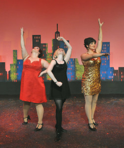 """Sweet Charity (Sarah Gore) bracketed by her Fandango Ballroom dance hall pals Nickie (Rebecca Campbell in red dress) and Helene (Haley Forsyth in gold dress) in Camelot Theatre's """"Sweet Charity""""."""