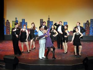 "Charity Valentine (Sarah Gore) dances with screen idol Vittorio Vidal (David King-Gabriel) as ensemble dances along in Camelot Theatre's ""Sweet Charity""."