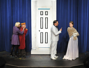 """David King-Gabriel (white tuxedo) gives a hilarious career-highlight performance as Italian film star Vittorio Vidal, with paramour Ursula (Holly Nienhaus in a great comedic turn as well) while Sweet Charity (Sarah Gore) puckers the doorman (George Herkert) in Camelot Theatre's """"Sweet Charity""""."""