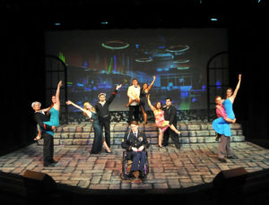 "Freddy (Eoghan McDowell) sits in wheelchair while Lawrence (Erik Connolly) and Christine (Sabrina Herbert), at top, dance in the ensemble number, ""The More We Dance"", with (left to right): Jake Hastings, &Carrie Ann Eve, Jasmin Evans & Dylan Spooner, Amanda McGee & Erny Rosales, Joey Larimer & Shannon Carter."