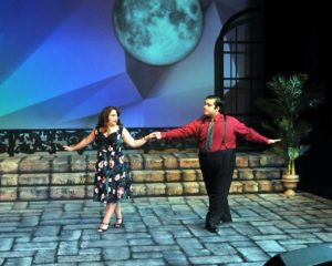 "In an amusing romantic subplot, ""eccentic supporting characters"" Muriel (Amanda McGee) & Andre (Ernie Rosales) present an adorable, beguiling couple, who in this scene are cutting up the dance floor."